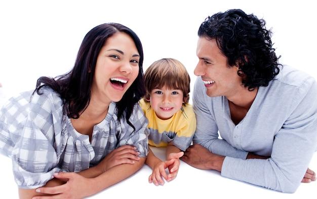 Lachende ouders met hun zoon op de vloer liggen