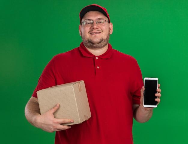 Lachende overgewicht jonge bezorger in optische glazen met kartonnen doos en telefoon geïsoleerd op groene muur met kopie ruimte