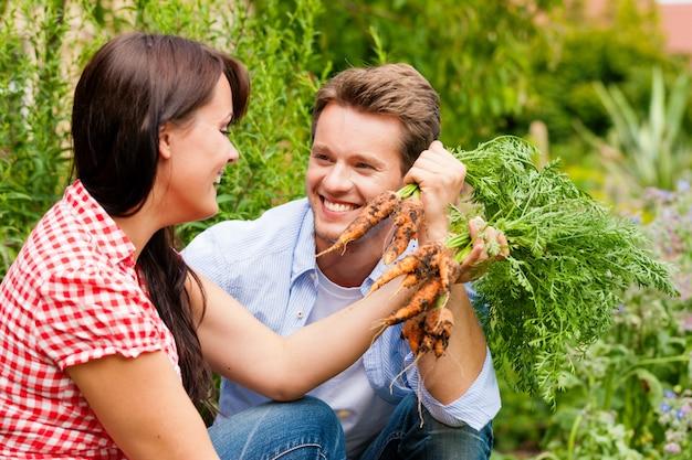 Lachende paar oogsten wortelen