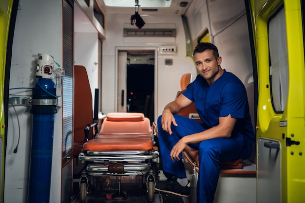 Lachende paramedicus in een blauwe uniform zitten in de achterkant van een ambulance auto