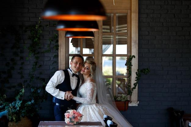 Lachende pasgetrouwden knuffelen bij het raam binnen. portret van pasgetrouwden in stijlvolle hotelkamer. bruidspaar in een kamer met een stijlvol interieur met lampen. trouwdag