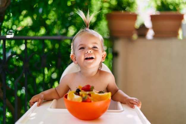 Lachende peuter zittend op een hoge stoel op het balkon voor een fruitschaal