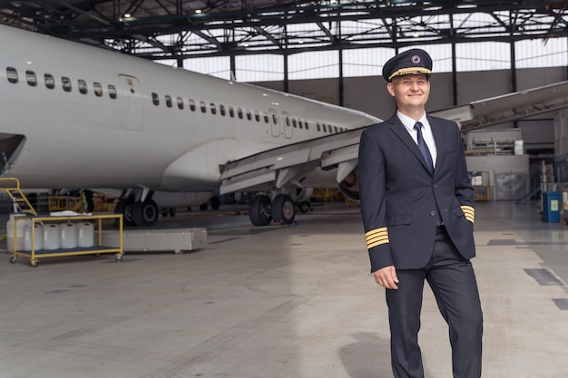 Lachende piloot poseren tegen de achtergrond van het vliegtuig in de hangar