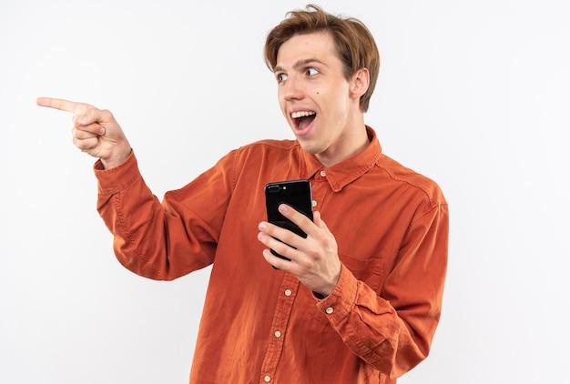 Lachende punten aan de zijkant jonge knappe kerel met een rood shirt met telefoon geïsoleerd op een witte muur