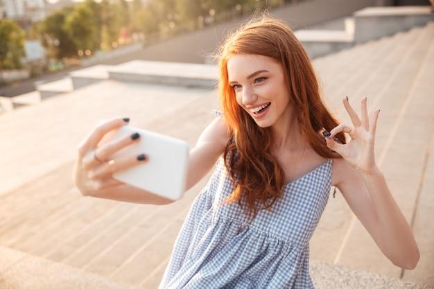 Lachende redhead vrouw met lang haar een selfie te nemen
