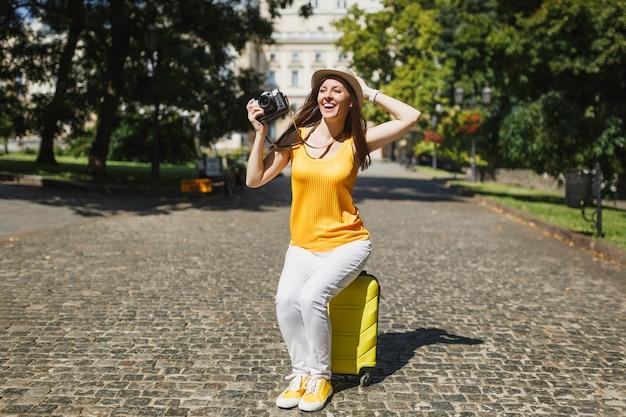 Lachende reiziger toeristische vrouw in hoed zittend op koffer met retro vintage fotocamera klampt zich vast aan het hoofd buiten. meisje dat naar het buitenland reist om een weekendje weg te reizen. toeristische reis levensstijl.