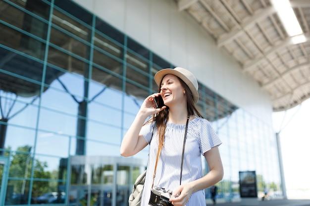Lachende reiziger toeristische vrouw met retro vintage fotocamera praten op mobiele telefoon bellen vriend,