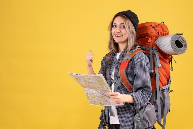 Lachende reiziger vrouw met rugzak met kaart wijzend naar