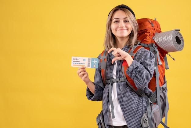 Lachende reiziger vrouw met rugzak met ticket