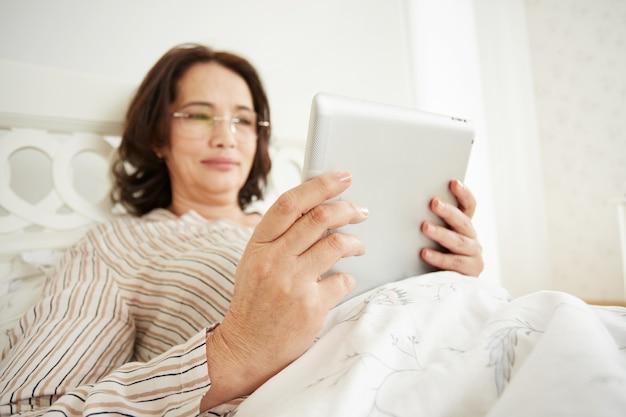 Lachende rijpe vrouw in glazen met behulp van digitale tablet-pc liggend op haar bed in een slaapkamer