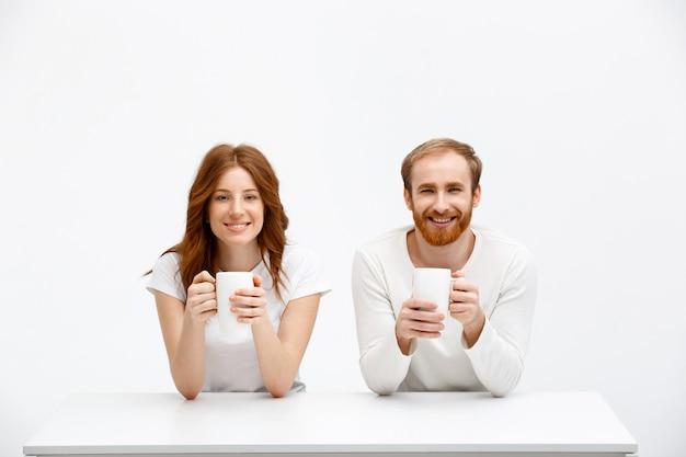 Lachende roodharige broers en zussen drinken koffie