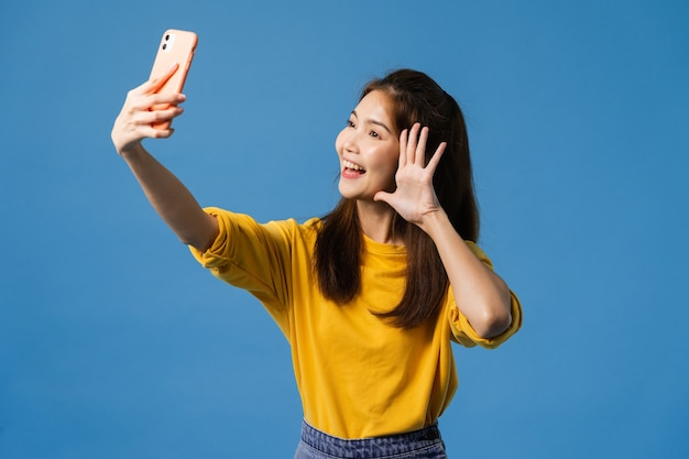 Lachende schattige aziatische vrouw selfie foto maken op slimme telefoon met positieve uitdrukking in casual kleding en stand geïsoleerd op blauwe achtergrond. gelukkige schattige blije vrouw verheugt zich over succes.