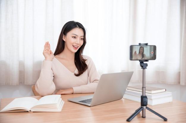 Lachende schattige jonge aziatische vrouw blogger video-opname