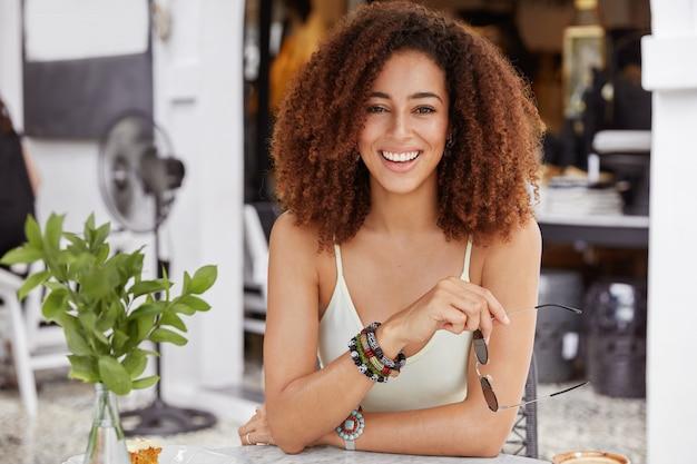 Lachende schattige jonge vrouw met borstelige kapsel, nonchalant gekleed, zonnebril houdt, vrije tijd doorbrengt in de coffeeshop, informele bijeenkomst heeft.