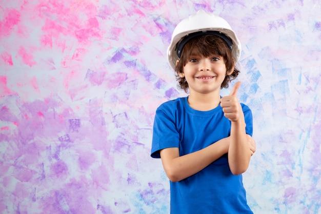 Lachende schattige jongen in blauw t-shirt en witte helm op veelkleurige