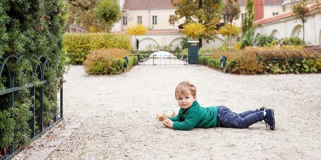 Lachende schattige kleine jongen liggend en spelen op aarde in het park. mooie kleine jongen in de herfst tuin. buitenactiviteiten voor kinderen. kopieer ruimte