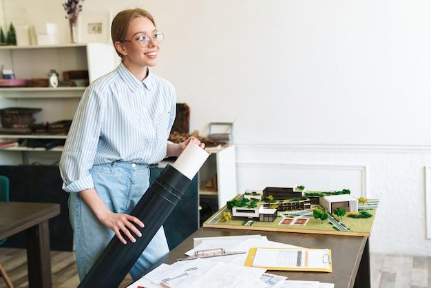 Lachende schattige vrouw architect in brillen werken met tekeningen tijdens het ontwerpen van concept op de werkplek