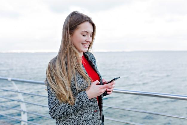 Lachende schattige vrouw in grijze jas en rood shirt scrollende smartphone aan de kade en geniet van mooi weer