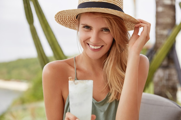 Lachende schattige vrouw met gelukkige uitdrukking heeft zomervakantie, besteedt vrije tijd op terras met vers koud drankje, ziet er positief uit. aantrekkelijk wijfje dat in strohoed in goed humeur is.