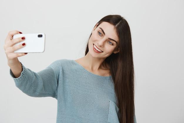 Lachende schattige vrouw selfie te nemen op smartphone