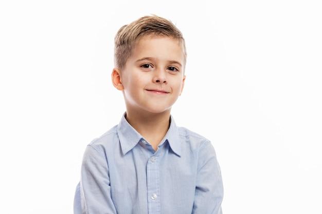 Lachende schoolgaande jongen met veranderende voortanden in een blauw overhemd. op wit wordt geïsoleerd