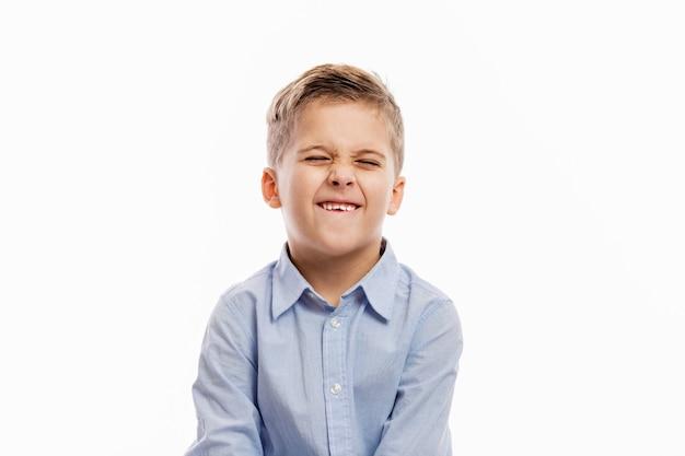 Lachende schooljongen in een blauw overhemd. op wit wordt geïsoleerd
