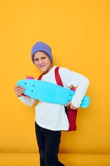 Lachende schooljongen met rode rugzak blauwe skateboard jeugd levensstijl concept