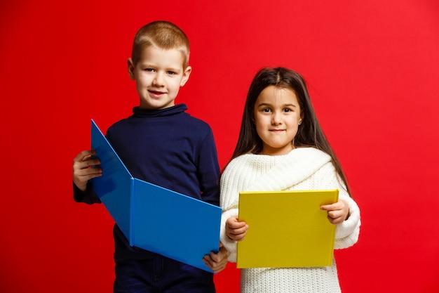 Lachende schoolkinderen lezen van een boek geïsoleerd op rode achtergrond