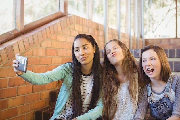 Lachende schoolmeisjes zittend op de trap selfie met mobiele telefoon te nemen