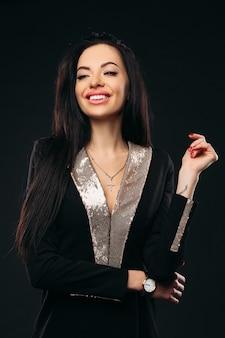 Lachende schoonheid in zwarte en gouden jurk.