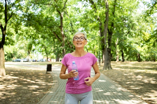 Lachende senior blanke vrouw joggen in het park.