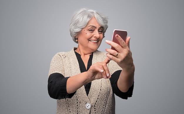 Lachende senior dame selfie te nemen
