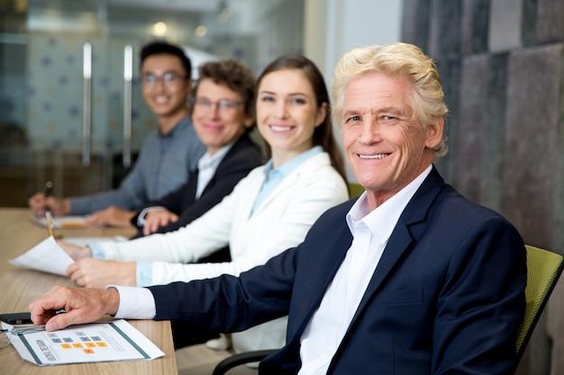Lachende senior leader op vergadering met zijn team