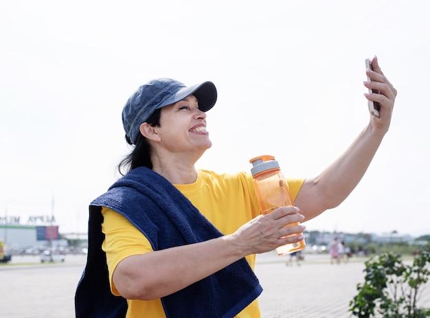 Lachende senior sportvrouw selfie buiten in het park doen