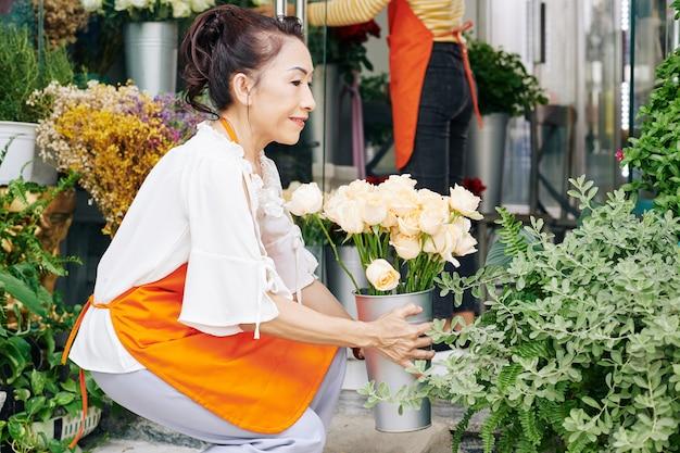 Lachende senior vietnamese vrouw emmers met bloemen in haar winkel schikken