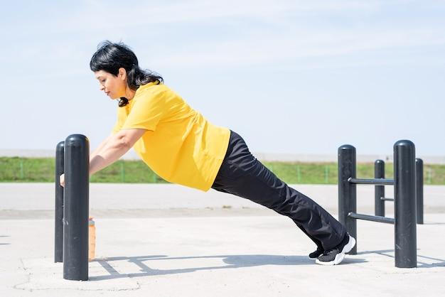 Lachende senior vrouw doet push-ups buiten op de sportveld bars