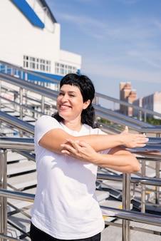 Lachende senior vrouw doet zich uitstrekt buiten op stedelijke scène