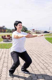 Lachende senior vrouw, gehurkt buiten in het park