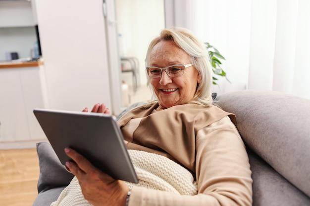 Lachende senior vrouw liggend op de bank thuis tijdens lockdown en opknoping op sociale media op zondagmiddag.