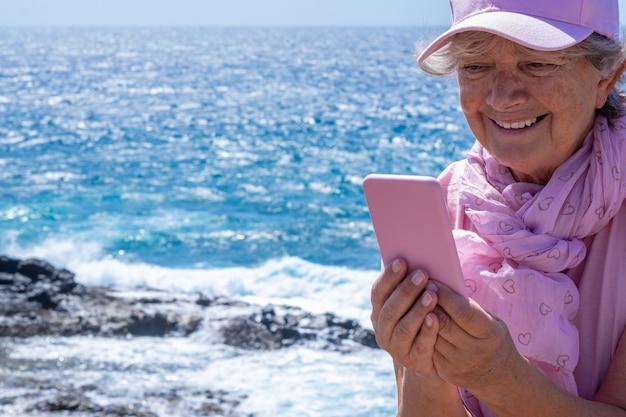 Lachende senior vrouw, roze gekleed, met behulp van telefoon op zee in winderige dag. senioren genieten van vakantie en schoonheid in de natuur