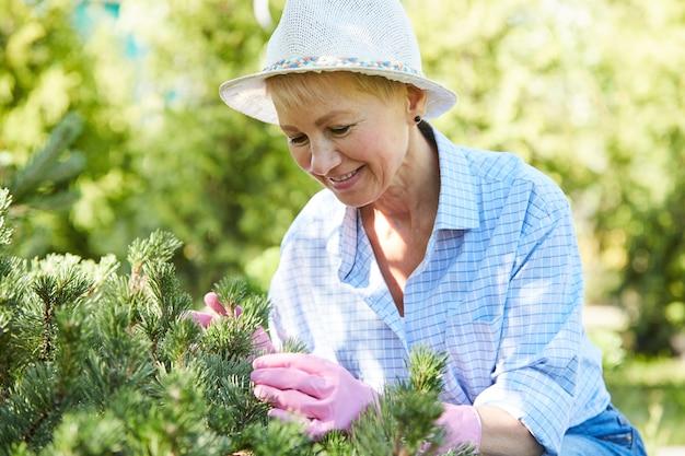 Lachende senior vrouw tuinieren