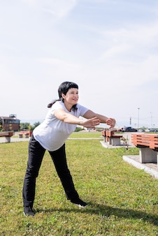 Lachende senior vrouw warming-up die zich uitstrekt buiten in het park