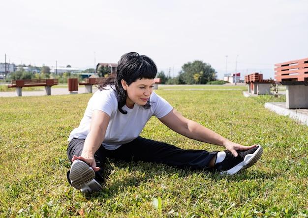 Lachende senior vrouw warming-up stretching zittend op het gras in het park