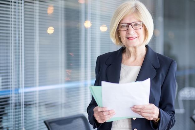 Lachende senior zakenvrouw bedrijf papieren