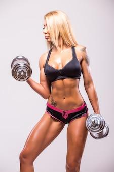 Lachende sexy atletische vrouw oppompen van spieren met halters op grijs