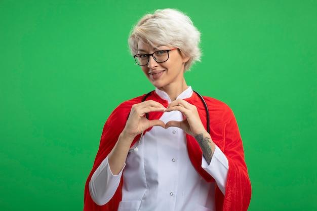 Lachende slavische superheld vrouw in uniform van de arts met rode cape en stethoscoop in optische glazen gebaren hart geïsoleerd op groene muur met kopie ruimte