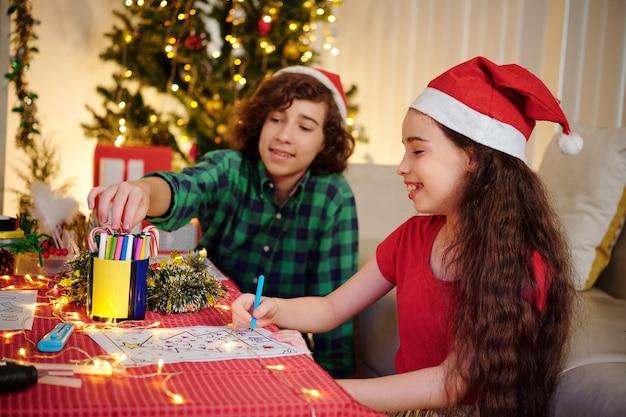 Lachende spaanse broer en zus in kerstmutsen die kersttekeningen kleuren met viltstiften