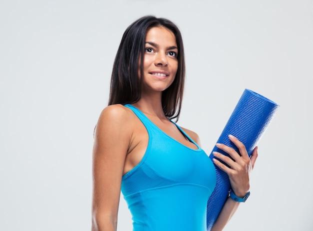 Lachende sport vrouw met yogamat