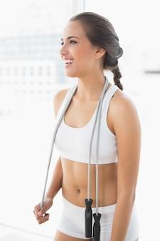 Lachende sportieve brunette draagt een springtouw rond de nek