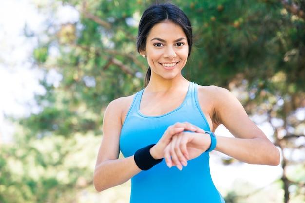 Lachende sportieve vrouw met behulp van slimme horloge buitenshuis